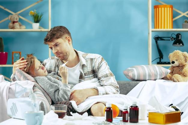 Chory mężczyzna z córką w domu. leczenie w domu. walka z chorobą. opieka medyczna. wolność rodzinna. zima, grypa, zdrowie, ból, rodzicielstwo, koncepcja relacji. relaks w domu