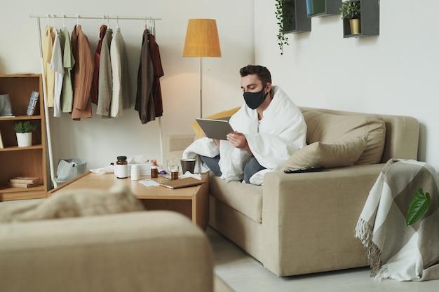 Chory mężczyzna z covid19 przy użyciu tabletu, siedząc na kanapie w salonie i pracując zdalnie w izolacji po podróży na wakacje