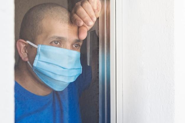 Chory mężczyzna z maską chirurgiczną wyglądający przez okno poddany kwarantannie w domu