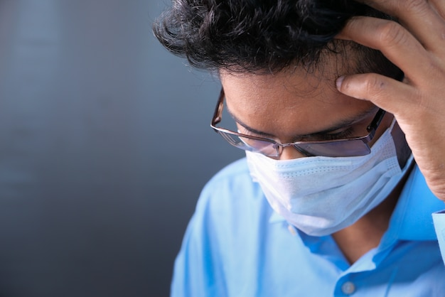 Chory mężczyzna z maską ochronną na twarzy patrząc w dół.