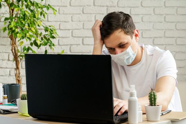 Chory mężczyzna z medyczną ochronną maską na jego twarzy pracuje w biurze. koncepcja wybuchu koronawirusa
