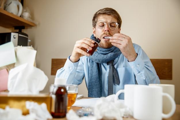 Chory mężczyzna z miksturą leczniczą pracujący w biurze, biznesmen przeziębiony, grypa sezonowa. pandemia grypy, zapobieganie chorobom, choroba, wirus, infekcja, temperatura, gorączka i koncepcja grypy