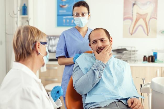 Chory mężczyzna z objawami bólu zęba trzymający rękę na policzku podczas rozmowy ze starszym lekarzem