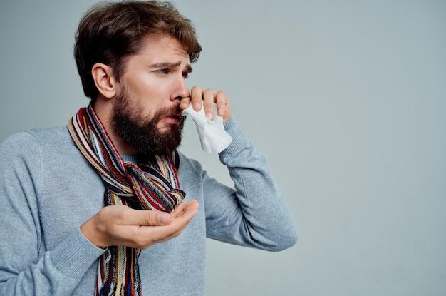Chory mężczyzna z szalikiem na szyi grypa problemy zdrowotne jasne tło