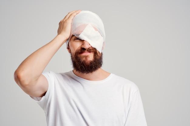 Chory mężczyzna z zabandażowaną głową i jasnym tłem hospitalizacji oczu