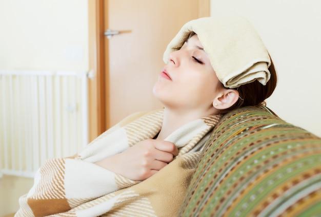 Chory młoda kobieta używa chusteczki na jej głowie