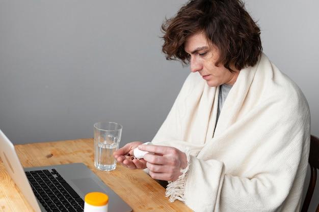 Chory młody człowiek rozmawia ze swoim lekarzem przez wideokonferencję