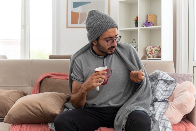 Chory młody człowiek w okularach optycznych owinięty w kratę, ubrany w czapkę zimową, trzymający kubek i patrzący na blistry z lekarstwami, siedzący na kanapie w salonie