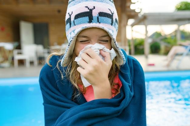 Chory nastolatek kobieta siedzi w ciepłym kapeluszu pod kocem z serwetką
