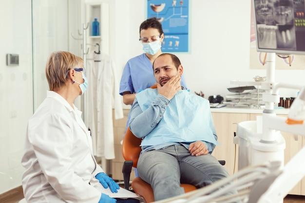 Chory pacjent skarży się na ból zęba podczas rozmowy z dentystą przed interwencją