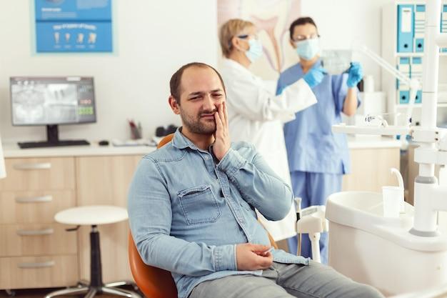 Chory pacjent skarży się na ból zębów w oczekiwaniu na dentystę, który sprawdzi ból zęba