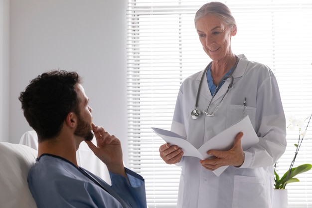 Chory pacjent w łóżku rozmawia z pielęgniarką