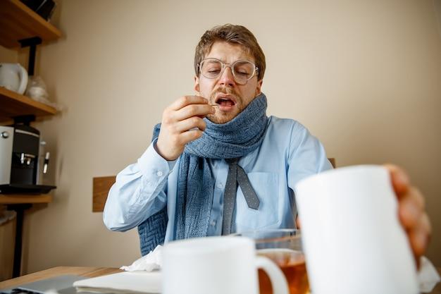 Chory podczas pracy w biurze biznesmen przeziębił się, grypa sezonowa.