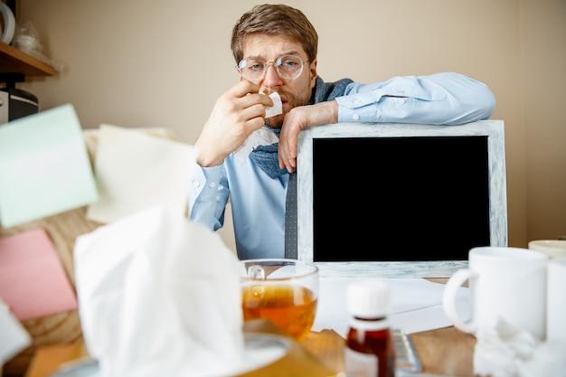 Chory podczas pracy w biurze, biznesmen przeziębił się, grypa sezonowa.