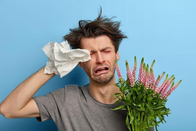 Chory przygnębiony młody człowiek przeciera oczy chusteczką, ma alergię na sezonowe kwiaty lub rośliny, płacze nieszczęśliwie, zmęczony walką z alergenami, potrzebuje dobrych zabiegów, stoi w domu