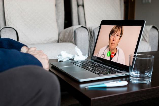 Chory słucha zaleceń lekarza podczas prowadzenia rozmowy wideo ze swojego komputera