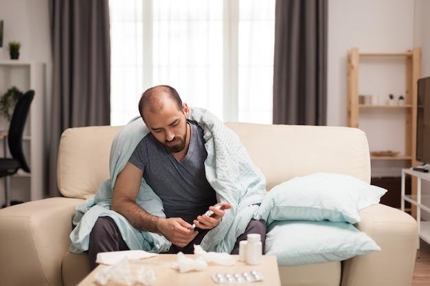 Chory sprawdza swoje pigułki podczas samoizolacji.