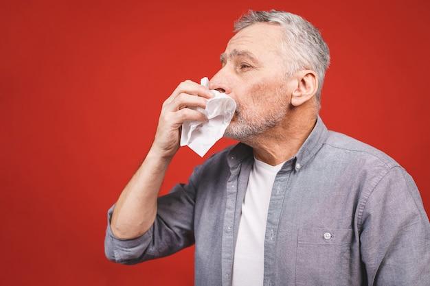 Chory starszy mężczyzna dmucha nos chusteczką. mając grypę, aller