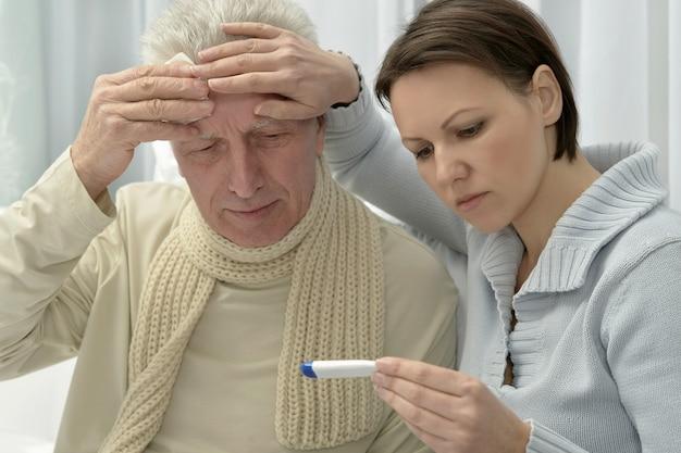 Chory starszy mężczyzna i troskliwa córka z termometrem