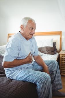 Chory starszy mężczyzna trzyma żołądek