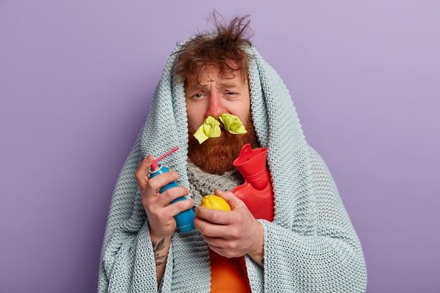 Chory w ciepłym ubraniu ze sprayem na nos, cytryną i workiem na wodę