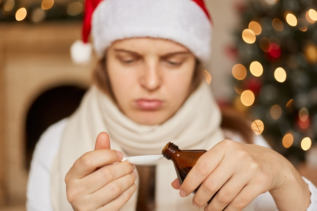 Chory w nowy rok! smutna chora kobieta w czapce mikołaja i białym szaliku siedząca z lekarstwem w rękach, musi pić syrop na kaszel, wlewając go łyżką.