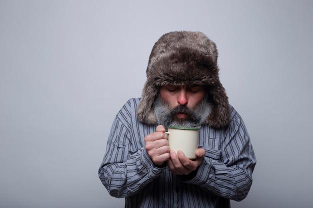 Chory w piżamie i czapce dmuchającej filiżankę gorącej herbaty