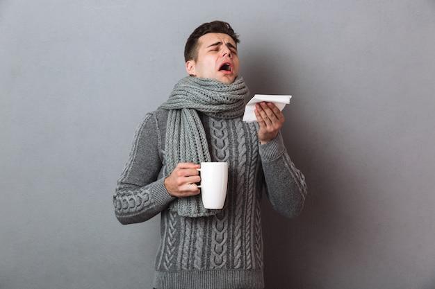 Chory w swetrze i szaliku kicha, trzymając filiżankę herbaty