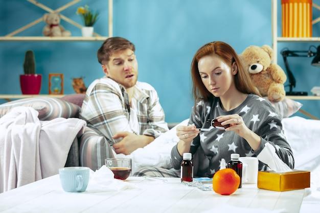 Chory z gorączką leżący w łóżku z gorączką. opiekuje się nim jego żona. choroba, grypa, ból, koncepcja rodziny. relaks w domu. koncepcje opieki zdrowotnej.