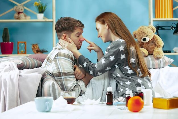 Chory z gorączką leżący w łóżku z gorączką.
