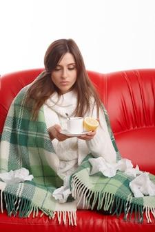 Chorych młoda kobieta, patrząc na jej filiżankę herbaty