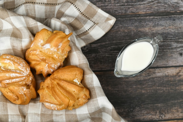Choux ciasto z mlekiem na ciemnym drewnianym. w koszu na ręczniku w kratkę. . szyk z twarogiem. małe ciasta kremowe w wiklinowej misce na drewniane