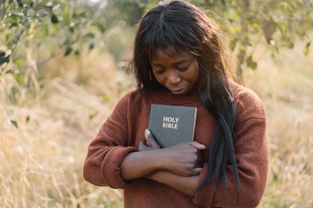 Christian afro dziewczyna trzyma biblię w dłoniach