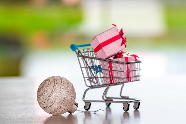 Christmas ball i koszyk z prezentami na niewyraźne tło, koncepcja świątecznych zakupów, skupienie się na piłce