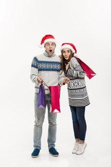 Christmas concept - pełnej długości młoda atrakcyjna para trzymając torby na zakupy samodzielnie na białej szarej ścianie.