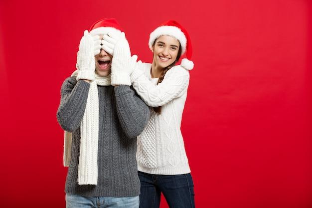 Christmas concept - portret uroczej dziewczyny zaskakujące zamknąć oczy swojego chłopaka w boże narodzenie.