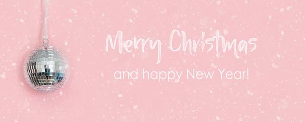 Christmas disco ball wiszące na różowo. kreatywna kartka świąteczna z życzeniami.