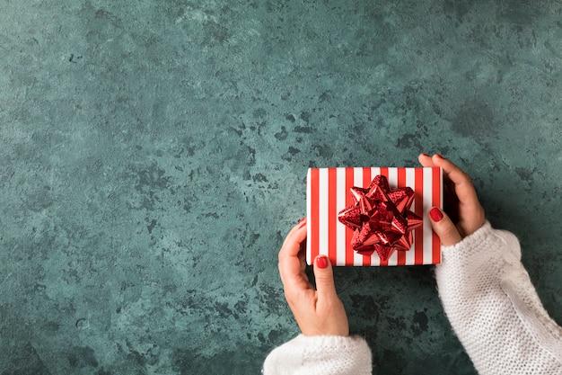 Christmas gift box w rękach kobiet. dekoracja tradycji