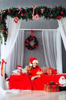 Christmas party girl piękna nastolatka w santa hat leżąca na czerwonym łóżku z jej prezentami obchody nowego roku