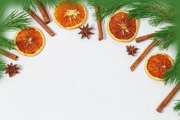 Christmas ramki z sosnowych gałęzi i przypraw, cynamonu, anyżu i pokrojone pomarańcze na tle