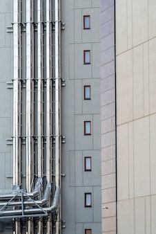 Chromowane rury wentylacyjne na ścianie nowoczesnego budynku elewacyjnego