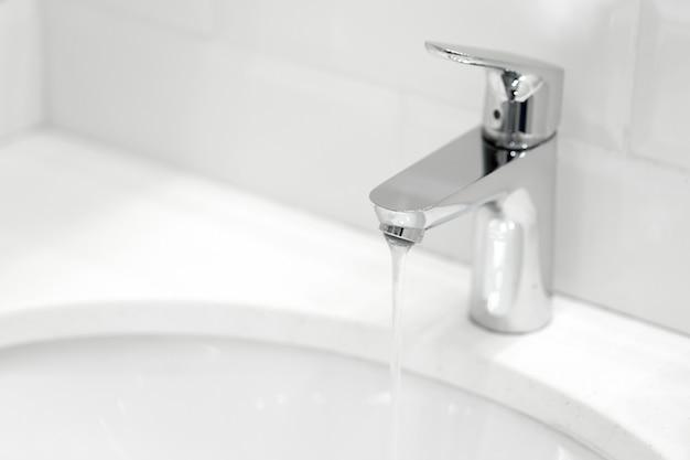 Chromowany żuraw na ceramicznej umywalce w łazience z bliska