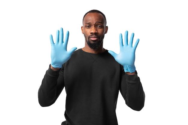 Chroń swoją skórę. mężczyzna ubrany w rękawice ochronne na białej ścianie.