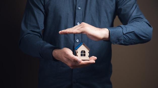 Chroni dom rękoma na brązowej powierzchni