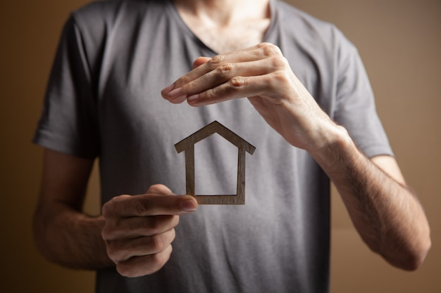 Chroni dom rękoma na brązowym tle