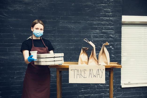 Chroniony. kobieta przygotowująca napoje i posiłki, nosząca maskę ochronną i rękawiczki. bezdotykowa usługa dostawy podczas pandemii koronawirusa kwarantanny. zabierz koncepcja. kubki do recyklingu, opakowania.