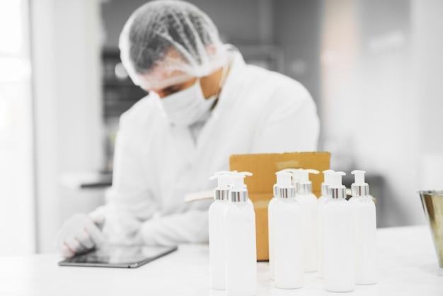 Chroniony naukowiec pakujący produkty kosmetyczne ze stołu laboratoryjnego podczas sprawdzania statusu na tablecie.