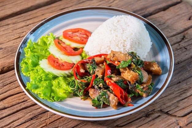 Chrupiąca bazylia wieprzowa z ryżem, podawana z sałatą, ogórkiem, pomidorem, ułóż piękne danie, postaw na drewnianym stole.