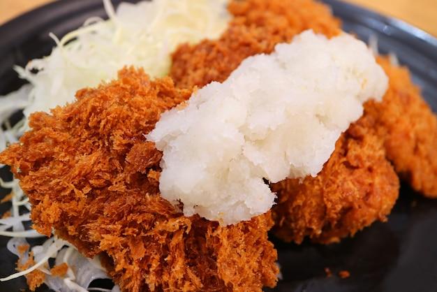 Chrupiąca konsystencja tonkatsu lub kotlet wieprzowy po japońsku z tartą rzodkiewką daikon