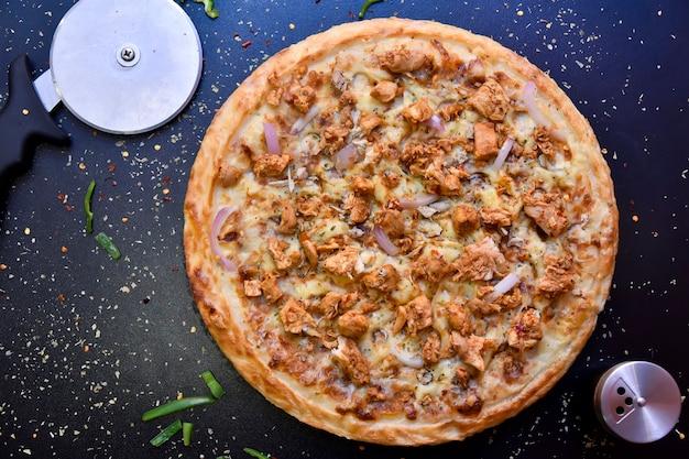 Chrupiąca pizza z widokiem z góry z oliwkami, kurczakiem, papryką i cebulą